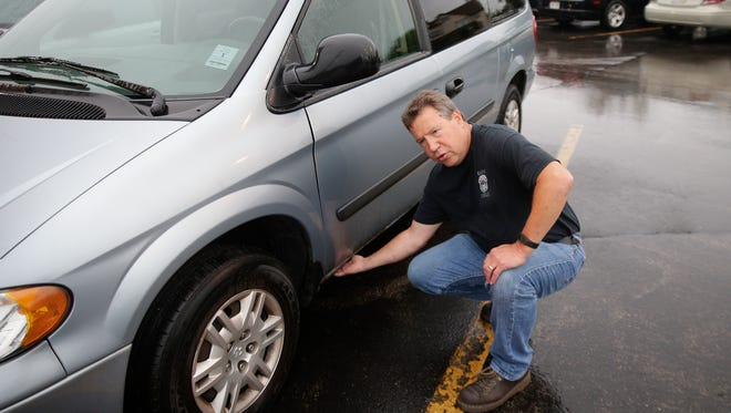 Dean Simon, head mechanic at the Green Bay Police Department, shows the rusted out floorboards of one of 10 vehicles being retired. This van has been used by a school resource officer and is no longer roadworthy.