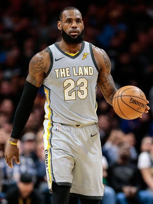 Cleveland Cavaliers forward LeBron James (23) dribbles the ball up court in the fourth quarter against the Denver Nuggets.