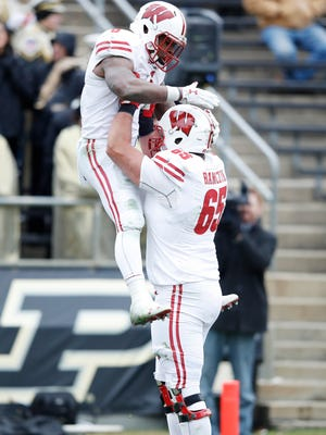 Corey Clement is lifted up by teammate Ryan Ramczyk after rushing for a six-yard touchdown against the Purdue Boilermakers.