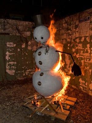 The 2014 snowman effigy begins to burn.