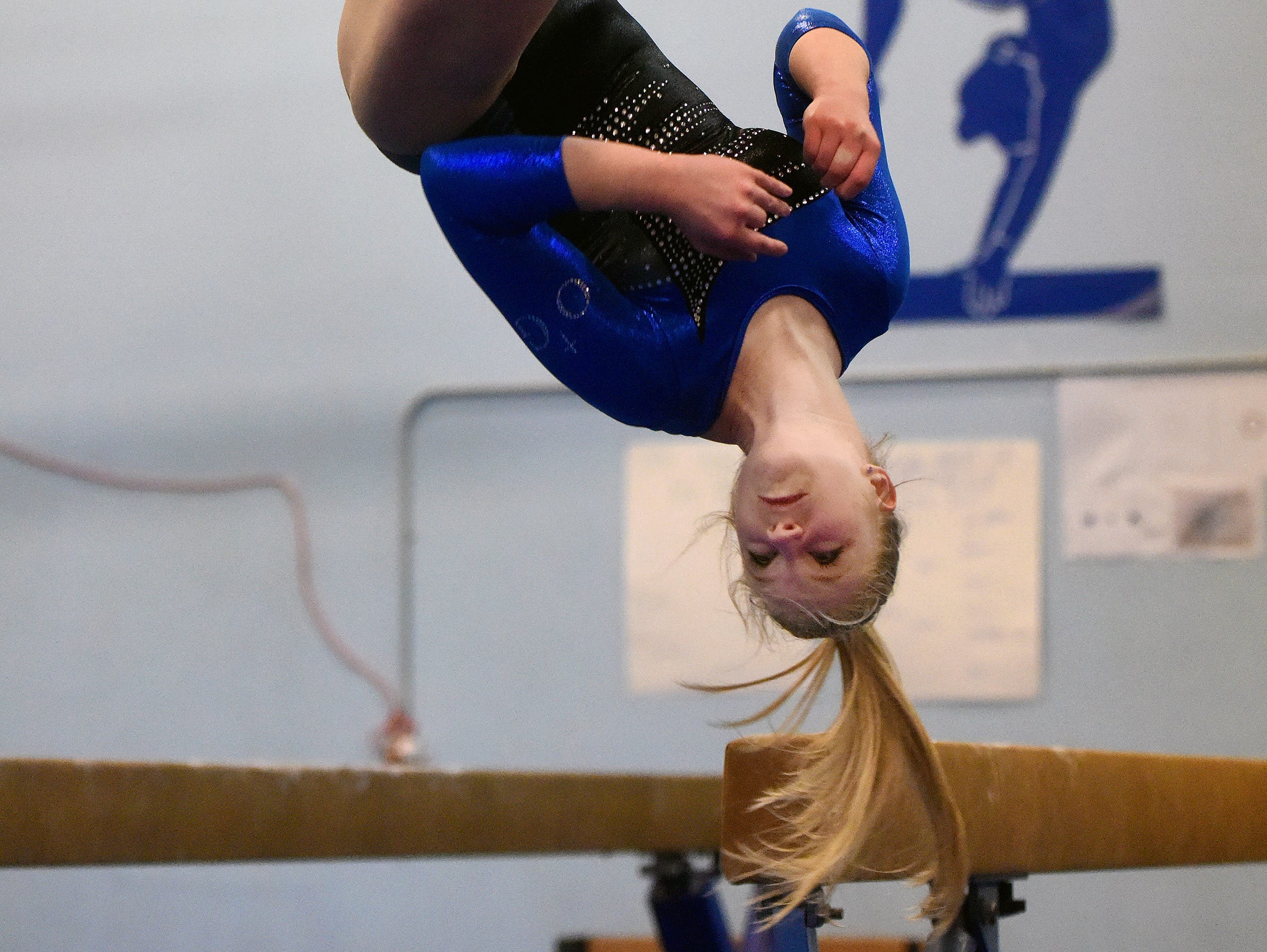 O'Gorman's Lizzie Miller practices dismounts off of the beam at Power and Grace Gymnastics.