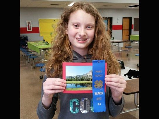 Mallory Morton displays her blue ribbon and winning