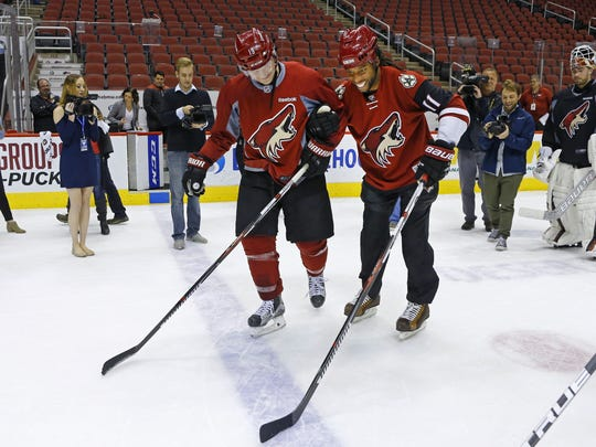 Shane Doan helps Larry Fitzgerald skate during Coyotes
