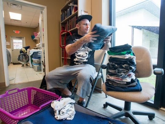 Jonathan Johnson folds his laundry at the Waterfront Rescue Mission in Pensacola on Wednesday, May 31, 2017.