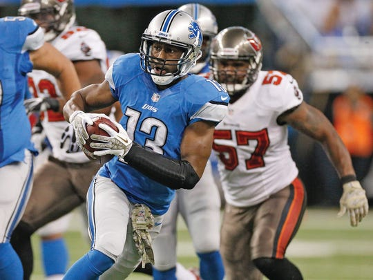 Nate Burleson (No. 13) of the Detroit Lions makes a catch and heads up field against the Tampa Bay Buccaneers at Ford Field on November 24, 2013 in Detroit, Michigan.