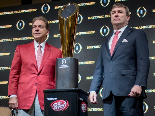 Alabama head coach Nick Saban and Georgia head coach Kirby Smart pose with the championship trophy during the coaches press conference for the College Football Playoff National Championship Game in Atlanta, Ga., on Sunday January 7, 2018. (Mickey Welsh / Montgomery Advertiser)