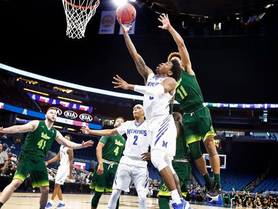 Memphis guard Kareem Brewton Jr. (front) drives for