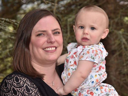 Emily Van Stedum holds her daughter Violet, 14 months,