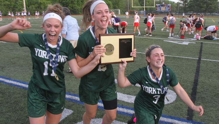 From left,Yorktown's Katie Comerford (17) Ashley Stilo(15) and Casey Duff (3) celebrate with the Section 1 plaque after defeating Somers 10-9 in the Section 1 Class B championship game at Mahopac High School May 26, 2016.