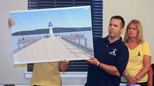 Ray Lennon, the brother of Mark Lennon, one of the two people killed in a boat crash on the Hudson River last year, displays a rendering of a proposed lighthouse to be built in Piermont. Lennon, along with Carol Stewart Kosik, the mother of Lindsey Stewart, the other person killed in the crash, made a presentation to the Piermont Board of Trustees on July 15.