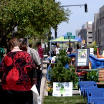 "Andy Kilpatrick, transportation engineer for the city of Lansing, takes a spin on Capitol Avenue. Around 18 parking spaces and the west traffic lane were converted into ""parklets"" for the public to enjoy."