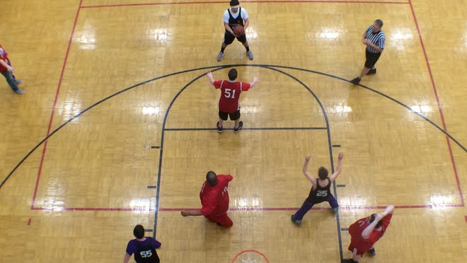 The North Scott Lancers in red and the Nodaway Valley Wolverines in black compete in the 3-on-3 basketball tournament during Saturday morning's Iowa Special Olympics Mid-Winter Tournament at the UI Field House.