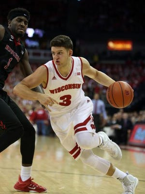 Wisconsin Badgers guard Zak Showalter (3) drives against Rutgers Scarlet Knights forward D.J. Foreman (1) at the Kohl Center. Wisconsin defeated Rutgers 79-57.