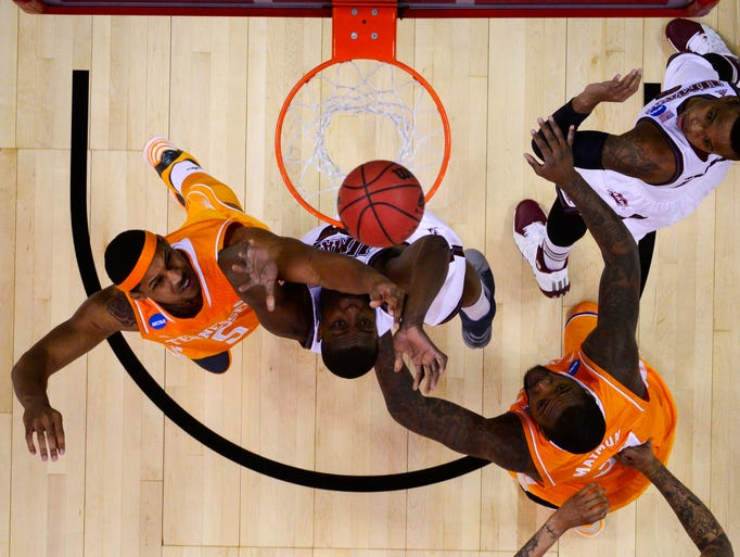 Massachusetts Minutemen forward/center Cady Lalanne (25) fights for a rebound with Tennessee Volunteers forward Jarnell Stokes (5) and forward Jeronne Maymon (34) in the first half of a men's college basketball game during the second round of the 2014 NCAA Tournament at PNC Arena. Mandatory Credit: Bob Donnan-USA TODAY Sports