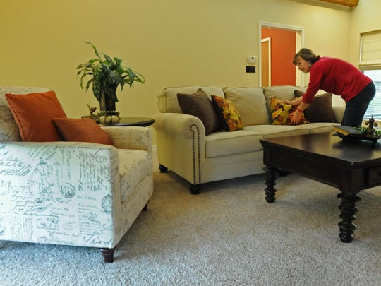 Claire Ellerbe adjusts the furniture and pillows to look just right as part of her home staging business, Staging Makes Sense.