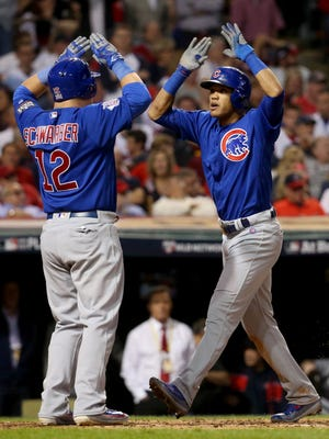 The Chicago Cubs' Addison Russell, right, celebrates with teammate Kyle Schwarber after Russell hit a grand slam in the third inning against the Cleveland Indians on Tuesday, Nov. 1, 2016, in Game 6 of the World Series at Progressive Field in Cleveland.