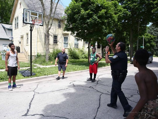 Milwaukee police officers play basketball with kids