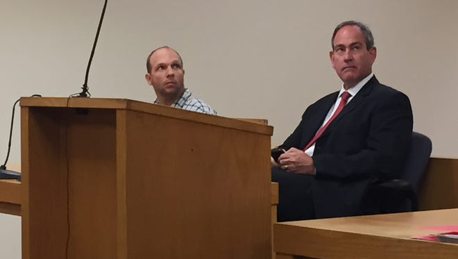 Christopher Scott, 28, of Goodland Township, left, and his attorney, Denis McCarthy, listen to John Miller, chief assistant prosecutor in Lapeer County, during Scott's preliminary exam July 8, 2015 in district court in Lapeer. Scott is facing an animal cruelty charge after shooting his dog in the head with a crossbow arrow in March. He said he was trying to euthanize the dog after it attacked and killed his pug, but the dog, named Gemma, survived the arrow to her head.
