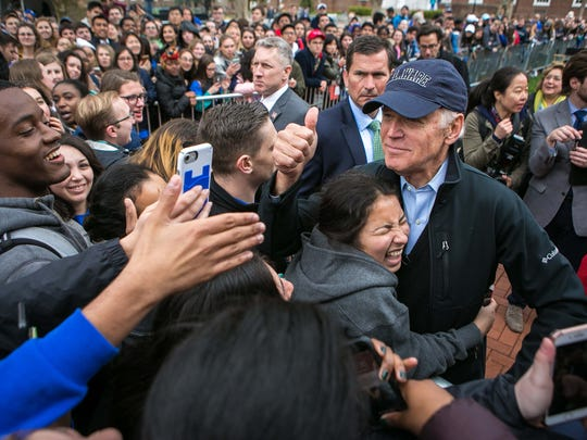 A student hugs UD alumnus and former Vice President Joe Biden who gives a thumbs up to students as he rolls through the crowd in his public return celebration on The Green at Memorial Hall.