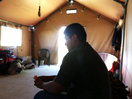 Jesus Herrera, 16, of Madera, Calif., tallies his work for the day at Reddout Orchard's campsite near Granger, Wash. on Thursday June 19, 2014. He sits in a tent that was rented from Washington state to be used as temporary farmworker housing.
