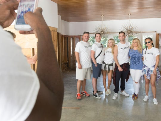 """Cast members of """"Rich Kids of Beverly Hills"""" pose for a photo with Maren Rosen, second from right, inside her flood-damaged home in the East Bayou neighborhood of Lafayette September 2, 2016."""
