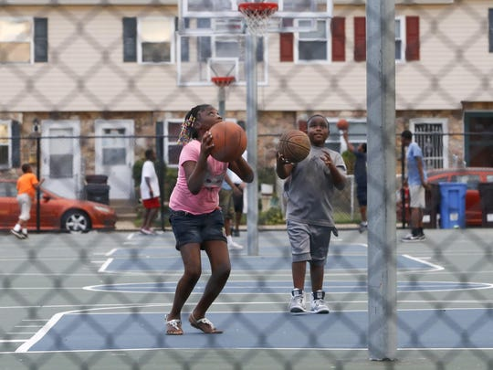 Children play on a ball court about a block away from where a 10-year-old boy was shot the day before in the Southbridge section of Wilmington.