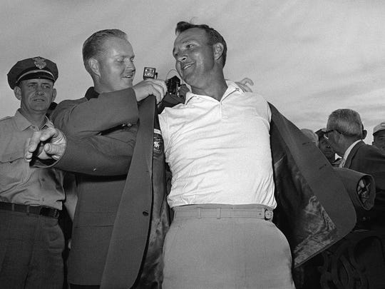 Arnold Palmer, right, slips into his green jacket with help from Jack Nicklaus after winning the 1964 Masters. Palmer, a four-time Masters champion, died Sunday in Pittsburgh. He was 87.