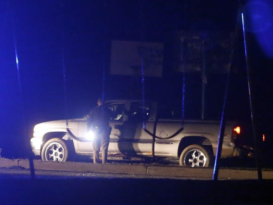 Police work at the scene of a double shooting reported shortly after 1 a.m. Sunday in Rogers Manor Park on Moores Lane near New Castle. Police investigated around a pickup truck with shattered windows parked on the grass.