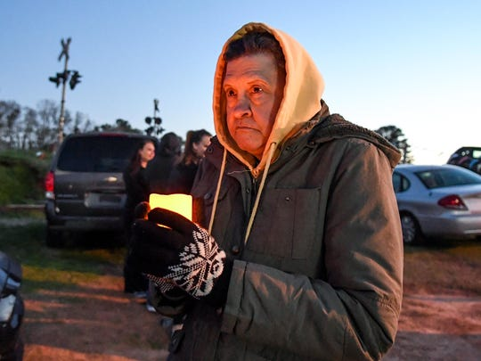 Valerie Remsen, of Williamston, holds a candle during a vigil for her missing son Bobby Shane Harvey, at the All Ride car business in Anderson, on Wednesday.