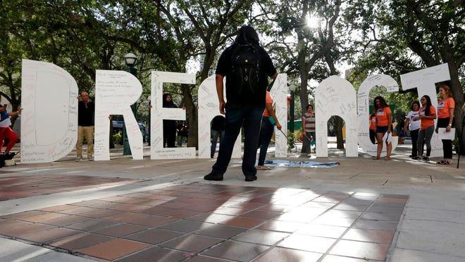 """File photo: Immigrant rights supporters hold giant letters reading """"Dream Act"""" as they demonstrate in favor of Congress passing a 'Clean Dream Act' that will prevent the deportation of young immigrants known as Dreamers working and studying in the U.S.,Friday, Oct. 13, 2017, in Miami."""