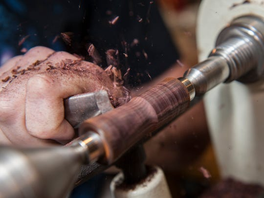 Wood shavings fly as Phil Sarullo of Madison patiently works the wood spinning on a lathe, shaping the body of what will become pen.