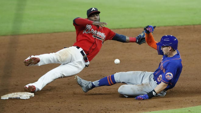 New York Mets' Brandon Nimmo (9) steals second base as the ball gets away from Atlanta Braves second baseman Adeiny Hechavarria (24) in the sixth inning of a baseball game Friday, July 31, 2020, in Atlanta. Nimmo advanced to third