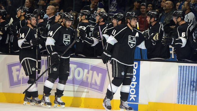 Los Angeles Kings right wing Justin Williams (14), center Dwight King (74) and center Anze Kopitar (11) go by the bench after a goal in the first period of the game against the Phoenix Coyotes at the Staples Center.