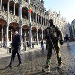 A soldier and a policeman patrol on the Grand Place as the Belgian capital remains on the highest possible alert level in Brussels.