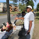 A woman gestures by a new teddy bear memorial on Tuesday, Sept. 23, 2014, in Ferguson, Mo., near the spot of where Michael Brown was shot by Ferguson police office Darren Wilson on Aug. 9. The original teddy bear memorial was destroyed by fire earlier Tuesday morning.