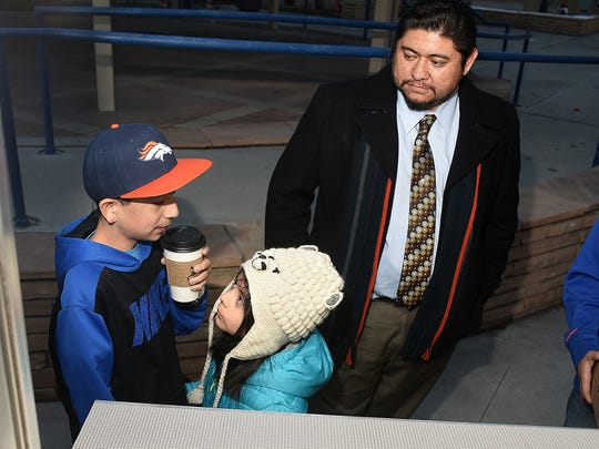 Izik Quinteros, 13, left, takes a sip of hot chocolate purchased from the Fox Hill Coffee Co. trailer as his sister, Esmia Quinteros, 7, waits for hers before the Farmington Christmas Parade on Thursday. At right is their father, Marcos Quinteros.