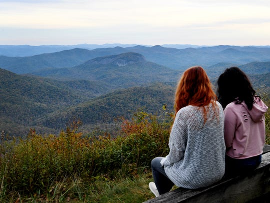 Marissa Burleson, left, and Dominique Marzan, both of Hendersonville, take in the view of Looking Glass Rock from the Blue Ridge Parkway October 21, 2017.