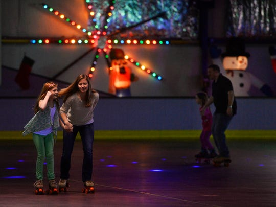 Laney Poulin, 9, left, of Red Lion, holds her mom Katie Poulin's hand as her husband Justin Poulin and daughter Alex Poulin, 7, skate behind at Roll 'R' Way roller skating rink in York . The family was continuing a four-year tradition of roller skating on Christmas Eve.