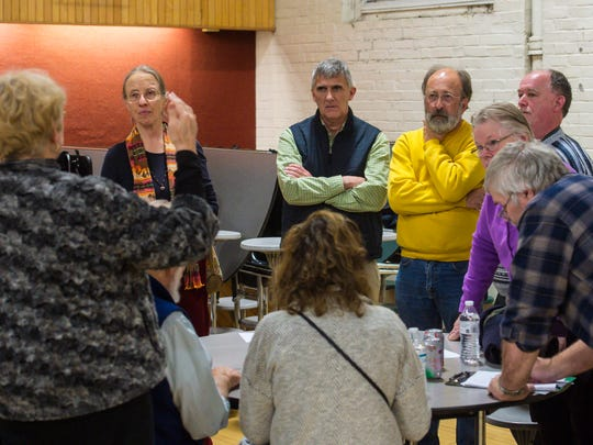 Burlington City Councilor Dave Hartnett, who ran as an independent in 2015 but won the Democratic endorsement this year, center, joins in as Burlington's Democrats chose their candidates for City Council during a caucus in Burlington on Thursday, January 12, 2017.  Hartnett was endorsed by Burlington Mayor Miro Weinberger.