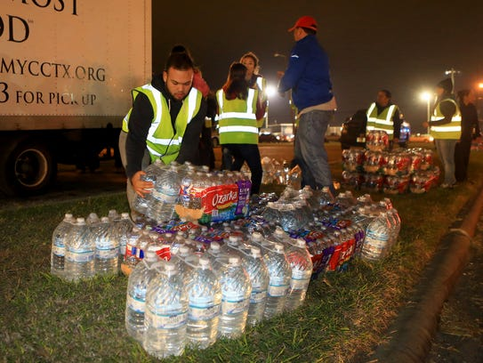 Volunteers pile cases of water to hand out to residents