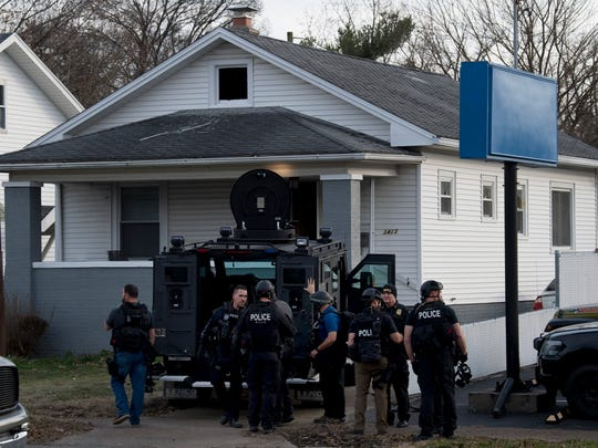 """Evansville Police Department SWAT team members gather outside a home at 1413 Washington Avenue after being given the order to stand down Monday afternoon. Police surrounded the home and put Washington Middle School and Bosse High School in """"secure mode"""" when a man escaped into the house while they were serving a warrant. The suspect eluded police."""