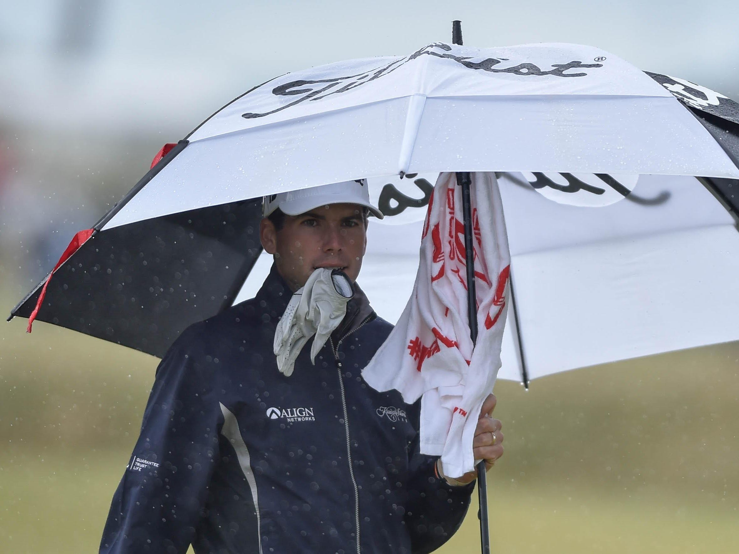 Ben Martin tries to keep dry during the third round of the 144th Open Championship at St. Andrews, Scotland.