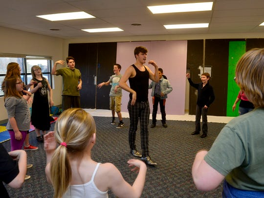 """Zachary Dennis, artistic director of NDM Productions, leads the cast of """"Willy Wonka and the Chocolate Factory"""" in warm up exercises during rehearsal March 10."""