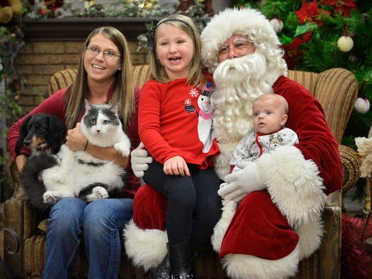 Anne Nihart, Waite Park, poses with Santa and her children, Ashlynn and Liam, dog, Tucker, and cat, Bambi, during the Santa Paws event Sunday at the Tri-County Humane Society.
