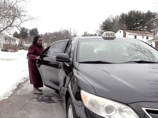 Deloris Ritchie of Hillcrest gets into a taxi to take