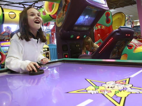 Kids with good report cards can get free game tokens at Chuck E. Cheese's. Here, Hannah Steinbrook, 8, plays a game of air hockey during a party at the East 82nd Street location in 2010.