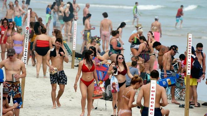 DAYTONA BEACH -- Spring Breakers along with beachgoers look to enjoy the beach along the shoreline in Daytona Beach on Monday, March 16.