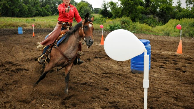 Haley Hodnefield of Clearwater aims to shoot a balloon on the course with her horse Lily as she practices for mounted shooting competitions  Aug. 21. In practice, Haley uses 25 grains of black powder. In competition, she'll use 33 1/2  grains.