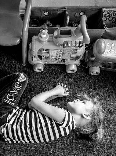"""Phoenix's """"happy place"""" is on the floor of her bedroom, playing with her toys that light up and make noise. Phoenix, 8, was diagnosed with autism spectrum disorder and is mostly nonverbal."""