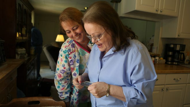 Debbie Corder, a caregiver, left, and Dolly Gregory look at old photos Oct. 16 of Gregory from when she was a firefighter in the 1970s. Corder comes to the Gregory's home three times a week to help with light chores and health care needs.